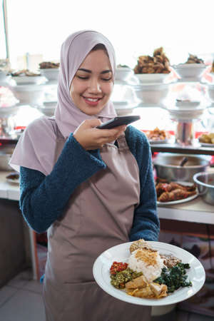portrait of young muslim woman take photos food