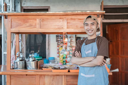 angkringan seller in apron smiles with crossed hands while standing Banque d'images