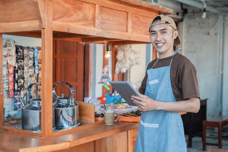Asian male seller in apron holding a tablet pc Banque d'images