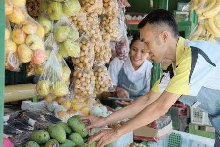 Couple using digital tablet while choosing mangoes 스톡 콘텐츠