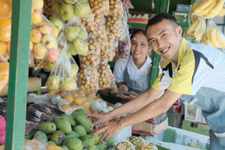 Smiling young man and woman sellers displaying assortment