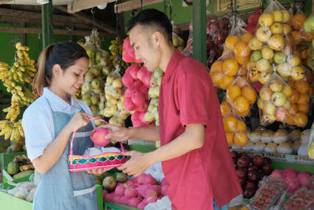 A smiling female shopkeeper in apron give service for male customers who want to buy fruit parcels 版權商用圖片 - 157404701