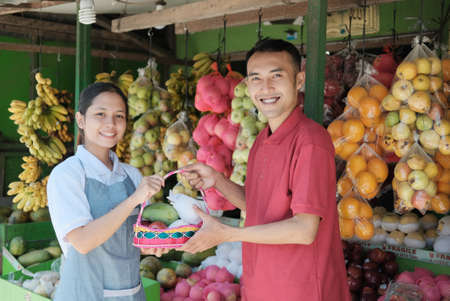 Female assistant helping customer at fruit counter Stock fotó