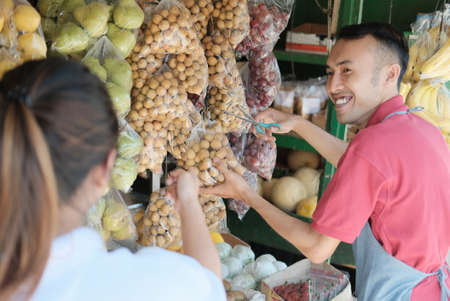 Asian male stall waiter smiles holding scissors while serving customers buying fresh fruit 스톡 콘텐츠