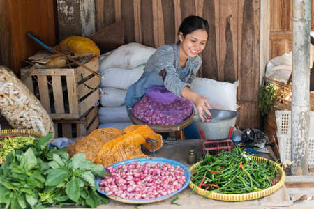 woman selling vegetables smiles while sitting with a sack filled with shallot