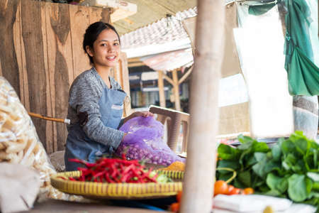 Asian greengrocer woman smiles as she pulls a red onion from a sack