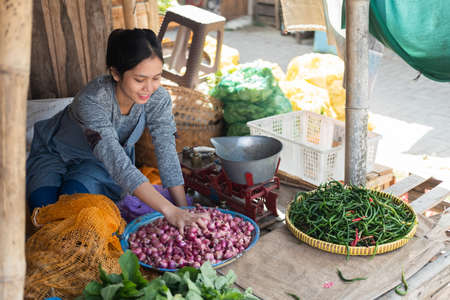 Asian greengrocer woman smiles while holding a shallot in a tray