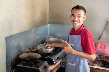 the male waiter smiles with a thumbs up while frying side dishes for customers
