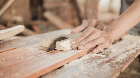 close up of a carpenters hand cutting wood planks using a circle saw