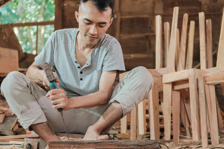 workers use chisels to carve wood for furniture