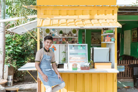 asian man small business owner at his shop made of truck container Foto de archivo