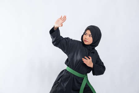 woman in hijab in pencak silat uniform poses stance and fend off attacks with copyspace