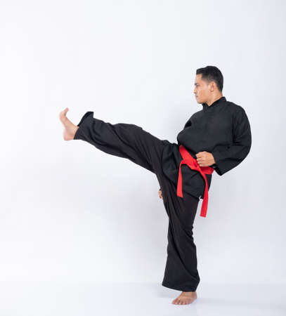 view side of an Asian man with an attacking pose kicking forward while wearing a pencak silat uniform 版權商用圖片