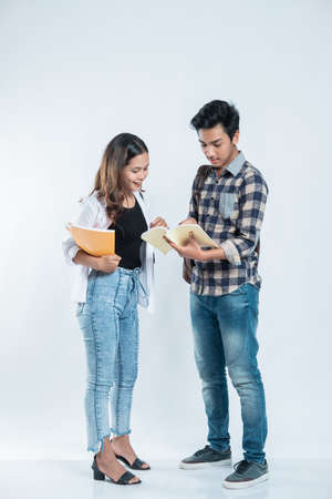 portrait young man explaining project on book to her partner