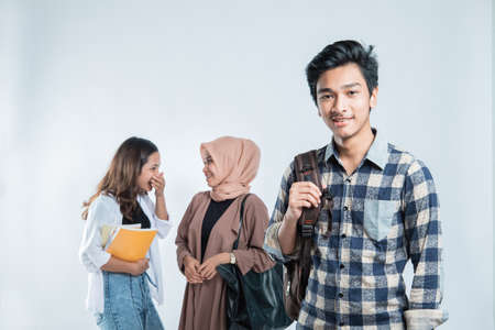 Portrait of Happy young man university carrying bags and campus young people chatting Standard-Bild
