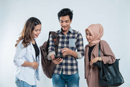 Portrait of happy university youth carrying bags and discussion looking at cell phones Standard-Bild