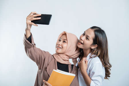 Portrait of happy university youth carrying a bag and taking a selfie with the cellphone