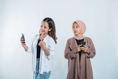 woman getting happy messages on a cellphone with college friends curious