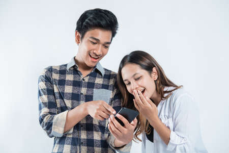 Portrait of happy university youth laugh happy discussion looking at cell phones Standard-Bild