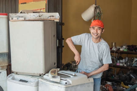 Asian electronics worker smiles at the camera using a screwdriver while repairing a washing machine