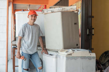 Asian electronics worker smiles at the camera holding a wrench standing next to a broken washing machine