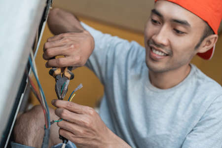 close up of an asian electronics worker using pliers to fix a washing machine cable that broke Standard-Bild