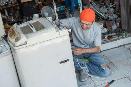 Asian male electronics worker fixing broken washing machine wiring