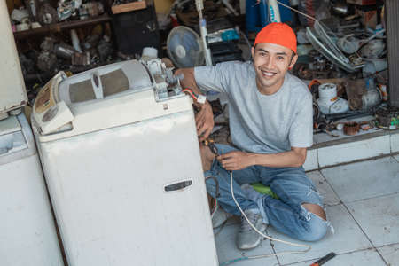 Asian male electronics worker smiles at the camera while repairing a broken washing machine cord