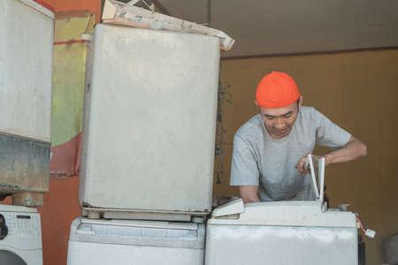 asian man electronics worker repairing broken washing machine tube