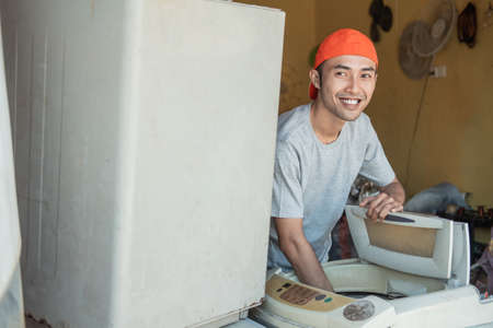 smiling asian male electronics worker looking at the camera as he unscrew the tube to fix a broken washing machine tube
