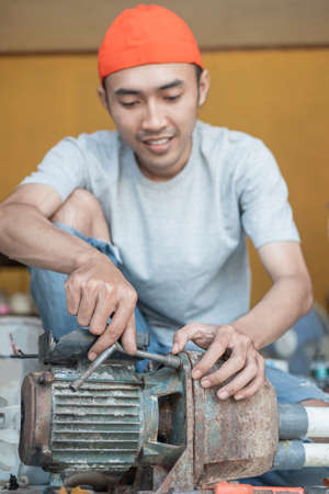 asian male electronics worker use three head wrench to repair water pump machine