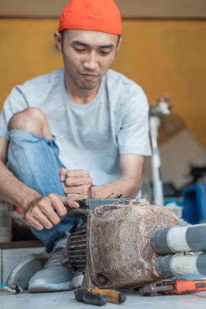 asian male electronics worker use three head wrench to unscrew when repairing water pump machine Standard-Bild