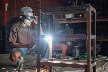 Squat welder wearing black welding glasses to make iron racks Standard-Bild