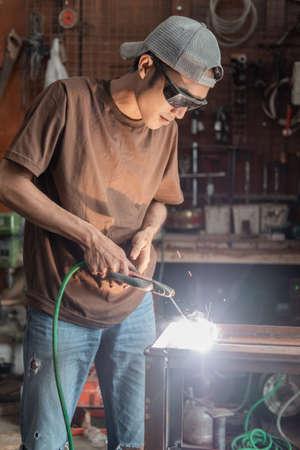 Welders stand up wearing black welding glasses when making metal racks Standard-Bild