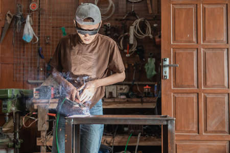 View from the front of A welder wearing black welding glasses while welding a metal rack Standard-Bild