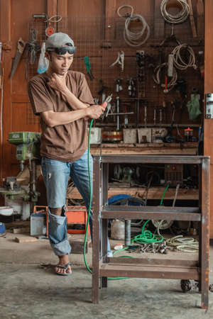 The welder thinks how to make a metal rack when holding an electric welder