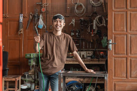 smiling welder looks into the camera while holding an electric welder