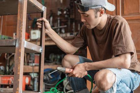 Asian welder holds an iron rack when welding using an electric welder