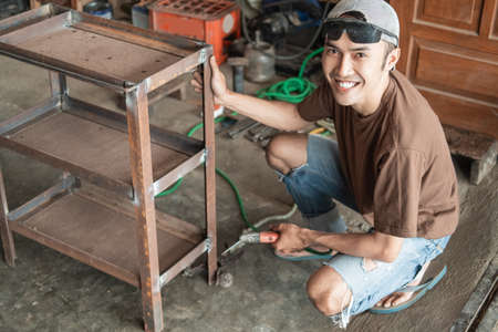 Asian welder smiles at the camera holding an iron rack while welding using an electric welder