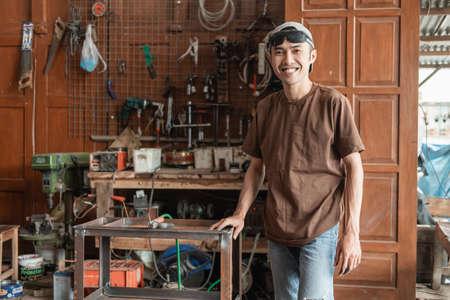 Male welder smiles at the camera holding a metal rack Standard-Bild