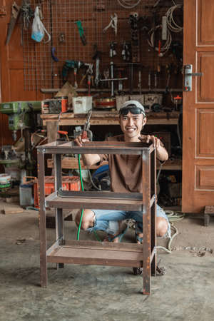 Squat male welder smiles at the camera holding an iron rack to weld Standard-Bild