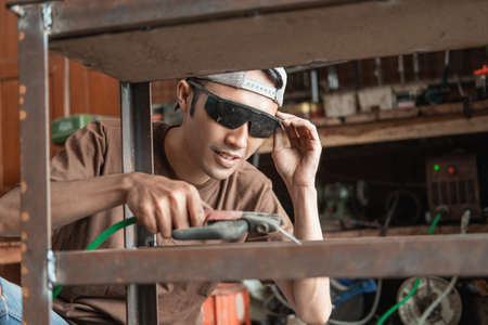 Squat male welder holding electric welder to weld iron frame