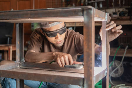 The male welder carefully uses electric welding to weld the metal frame