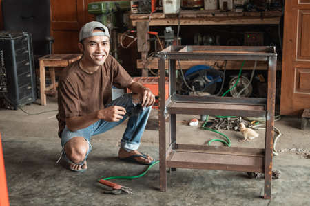 Smiling male welder squatting after using electric welding to weld metal frame