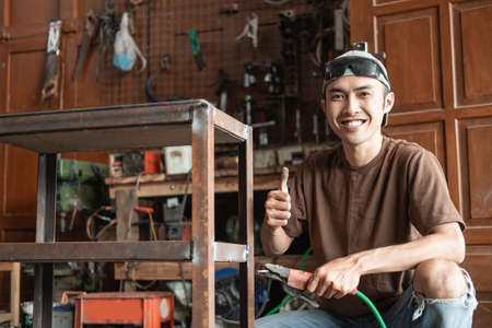 close up of Male welder smiling with a thumbs up while holding an electric welder