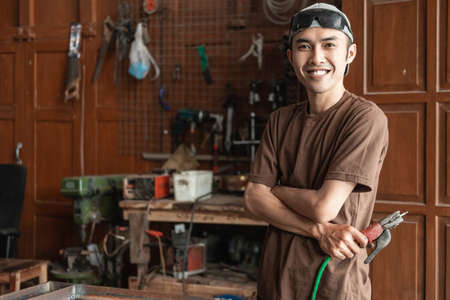Male welder smiles with crossed hands while holding electric welder