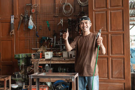 Asian male welder smiles with a thumbs up while holding an electric welder Standard-Bild