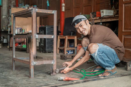 male welder smiles while holding the negative pole clamp for the electric welder