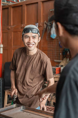 male welder smiles when asked to work according to the orders of the workshop business owner