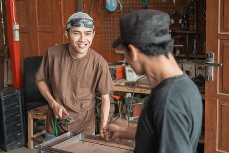 Welding workshop business owners tell their employees to complete work